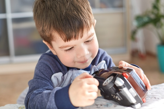 Indoor shot of good looking small kid holds toy car in hands