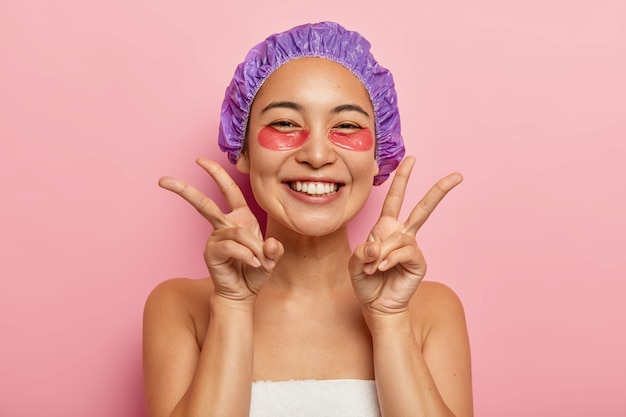 Indoor shot of good looking smiling asian girl make peace gesture with both hands, enjoys uder eye treatment, applies collagen patches, visits cosmetologist wears shower cap on head. face care concept