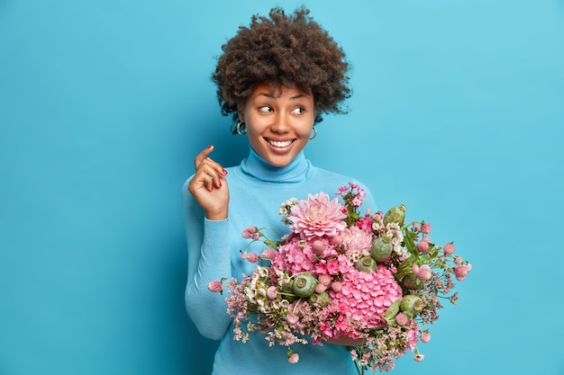 Indoor shot of good looking woman holds bouquet of flowers looks aside gladfully has delicate look dressed in casual turtleneck isolated over blue wall