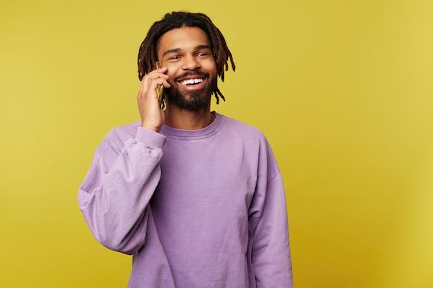 Tiro al coperto di bello giovane allegro uomo bruna dalla pelle scura sorridente volentieri pur avendo una piacevole conversazione telefonica, in piedi su sfondo giallo