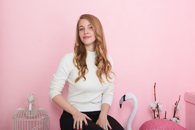 Indoor shot of gorgeous glamourous young european female with long wavy hair wearing stylish clothes, sitting against blank pink wall background with various interior items, smiling at camera happily