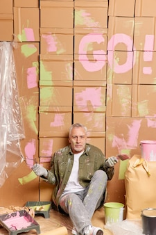 Indoor shot of grey haired man shrugs shoulders in hesitation surrounded with paint bucket and repairing tools sits on floor takes off glasses wears casual clothes. construction remodel or renovation