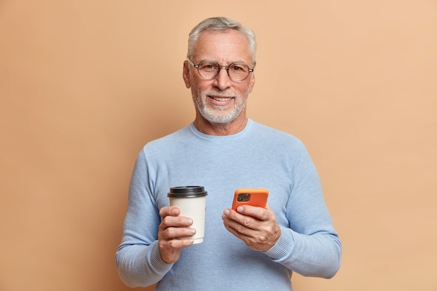 Indoor shot of handsome bearded mature man has free time after work checks social networks on smartphone drinks takeaway coffee wears spectacles and blue jumper isolated over brown wall