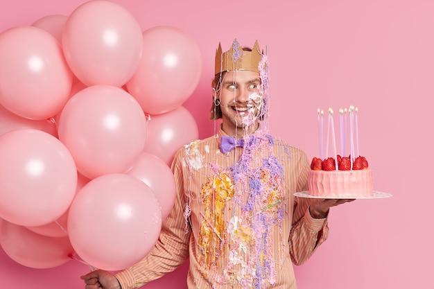 Tiro al coperto di bell'uomo allegro che celebra l'anniversario spalmato di crema detiene una deliziosa torta e palloncini si diverte alla festa di compleanno isolata sopra il muro rosa