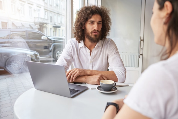 Indoor shot of handsome curly guy with beard having important conversation with business partner in cafe, sitting at table near window with folded hands