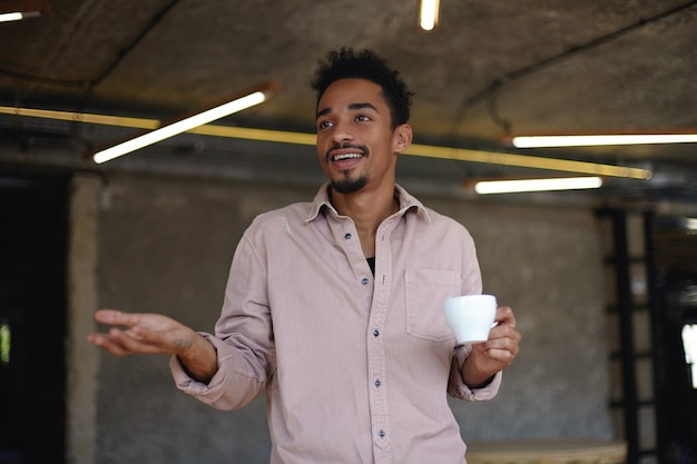 Indoor shot of handsome dark skinned bearded guy with short haircut posing over coworking space, shrugging and holding cup of tea in his hand, dressed in casual clothes