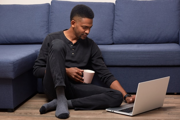 Indoor shot of handsome delighted man sitting near sofa at home, spending his weekends with laptop, surfing net, relaxing time