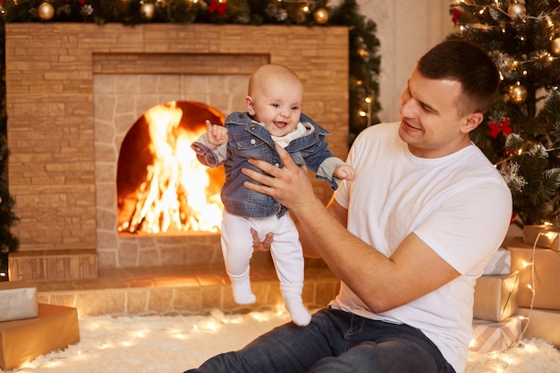 Indoor shot of handsome father wearing white casual t shirt holding little toddler daughter in hands while sitting near fireplace and xmas tree at home, happy new year.