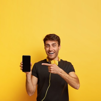 Indoor shot of handsome happy youngster holds mobile phone, points at display
