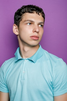 Indoor shot of handsome muscular guy with positive expression, wears casual mock up blue t shirt for your promotion, stands against purple background, free space aside. people and emotions.