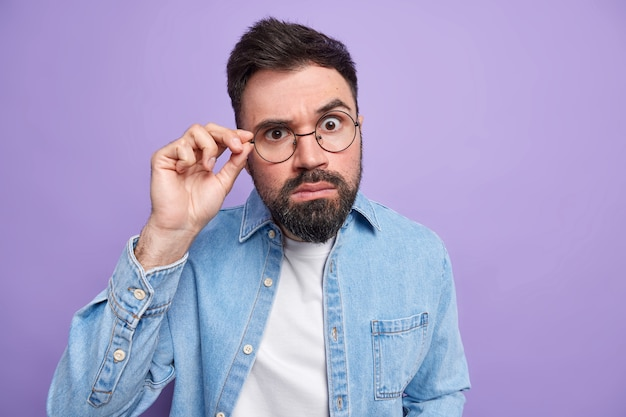 Indoor shot of handsome surprised adult man with thick beard looks attentively through round spectacles dressed in denim shirt hears exciting news stands speechless against purple wall