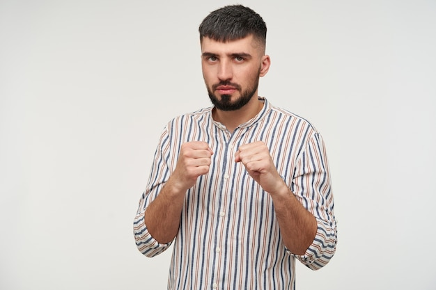 Indoor shot of handsome young brown-eyed brunette male with beard looking seriously  while standing over white wall in defensive position with raised fists