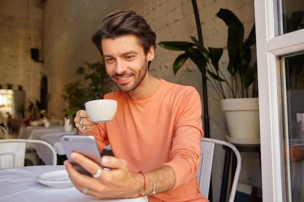 Tiro al coperto di bel giovane in maglione color pesca che beve caffè nel caffè della città vicino alla finestra, tenendo il telefono in mano guardando lo schermo