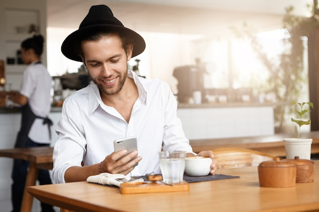 Indoor shot of handsome young man wearing hat and white shirt smiling happily while reading sms on mobile phone, messaging his girlfriend online using free wi-fi during lunch at cafe