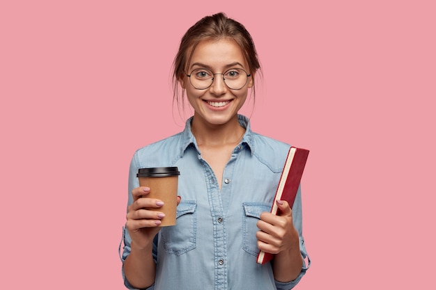 Indoor shot of happy caucasian female holds disposable cup of coffee
