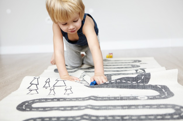 Indoor shot of happy cheerful caucasian two-year old boy with blonde hair playing with his toys, crawling on carpet in children's room, looking interested.