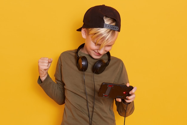Indoor shot of happy child, little boy in headphones around neck, fashionable kid listening music and playing online games, isolated on yellow wall. guy clenching hand, looks exited, celebrates win.