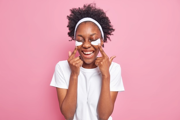 Indoor shot of happy dark skinned young woman with curly hair points at beauty patches under eyes smiles broadly