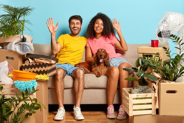 Indoor shot of happy diverse family couple wave, sit on comfortable sofa, pedigree dog lies near, celebrate moving day, have many boxes with belongings to unpack, being in good mood