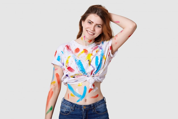 Indoor shot of happy european female painter has dirty body and white t shirt with colourful paints, shows belly, keeps hand behind head, isolated over white wall creats artwork or masterpiece