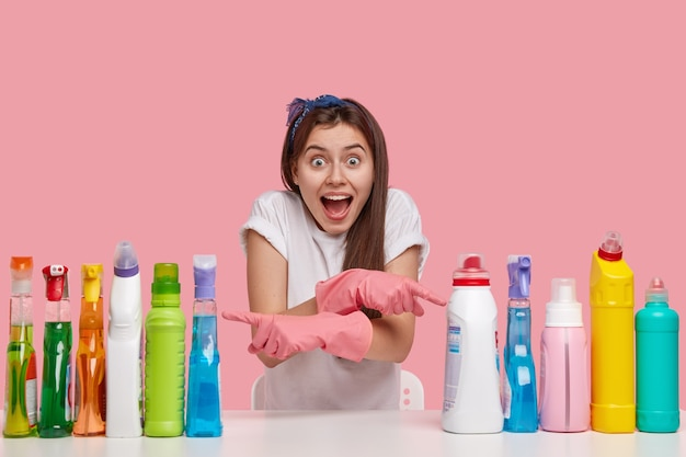 Indoor shot of happy european lady with overjoyed expression, keeps mouth opened, crosses hand and indicates at two sides on detergents