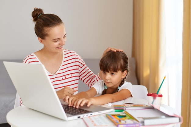 Indoor shot of happy family doing homework together, sitting at table in living room, mommy praises her daughter for school success, caress her little daughter, touching her head.