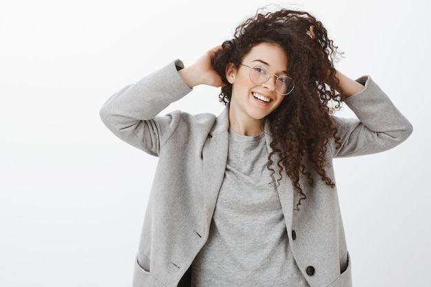 Indoor shot of happy fashionable female fashion blogger in stylih grey coat and glasses, touching curly hair and smiling broadly while tilting head and feeling awesome