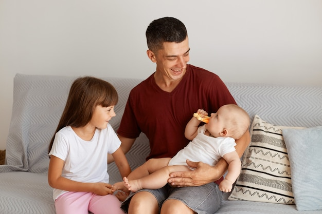 Indoor shot of happy father wearing burgundy casual style t shirt sitting on sofa with his daughters, looking with love and gentle at his infant child, laughing, enjoying spending time together.