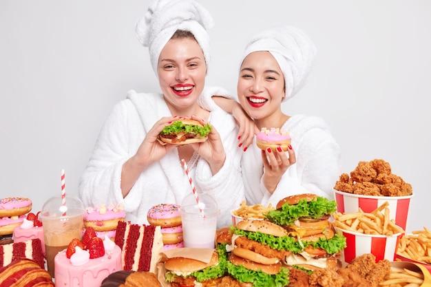 Indoor shot of happy female best friends eat junk food enjoy diet breakdown express positive emotions wear bathrobes towel on head red lipstck have fun together.