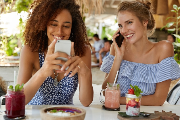 Indoor shot of happy females use modern smart phones, surf social networks and have mobile conversation, spend free time at cafeteria, drink smoothie. joyful women recreate during summer holiday
