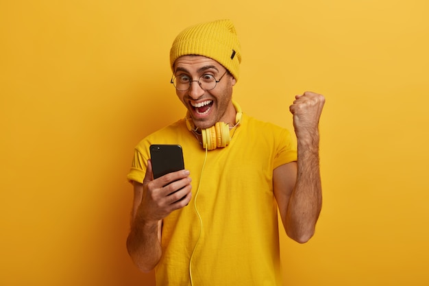 Indoor shot of happy man shows fist bump joyfully, uses cellphone, receives fantastic news, celebrates getting promotion, wears transparent glasses
