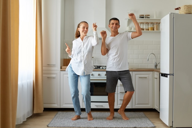 Indoor shot of happy positive husband and wife dancing, having fun together in kitchen, celebrating relocation, being in good mood, expressing happiness.
