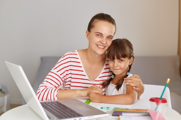 Indoor shot of happy positive woman with daughter, sitting at table with portable computer and books, female hugging her child, people looking art camera with optimistic expression.