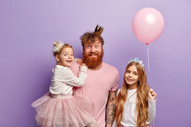 Tiro al coperto di felice uomo dai capelli rossi con corona sulla testa, porta una bellissima piccola figlia sulle mani, organizza una vacanza indimenticabile per la figlia nella giornata internazionale dei bambini. famiglia dello zenzero.