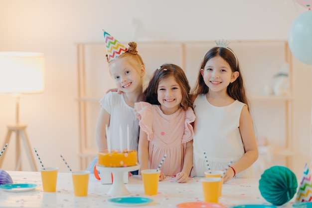 Indoor shot of happy three girls embrace and have fun, smile gladfully, stand near festive table with cake