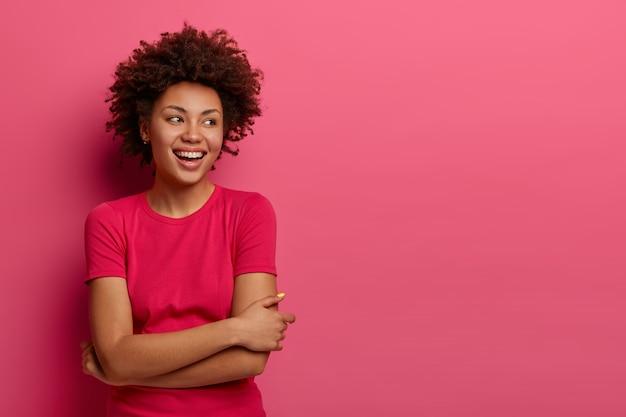 La ripresa interna di una donna felice tiene le braccia incrociate sul corpo, concentrata da parte con un ampio sorriso, gode di conversazioni informali con qualcuno, discute di qualcosa di divertente, posa in roseo. concetto di felicità
