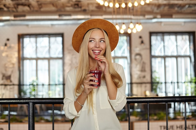 Indoor shot of happy young blonde woman with blue eyes standing over restaurant interior, drinking lemonade with straw and looking aside with dreamy smile