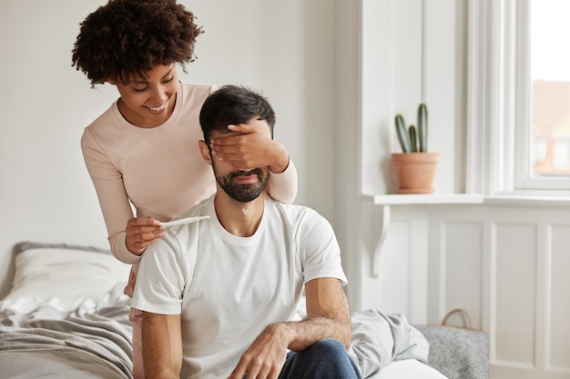 Tiro al coperto di felice coppia giovane con test di gravidanza in posa a casa