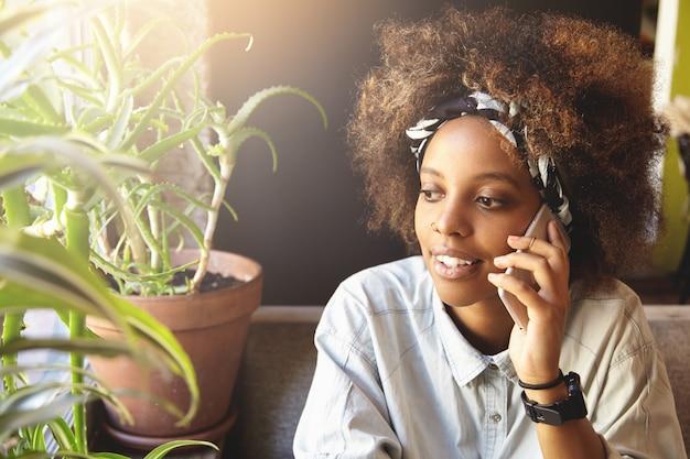 Tiro al coperto di felice giovane donna dalla carnagione scura utilizzando il telefono cellulare mentre si parla con gli amici, seduto alla finestra a casa.