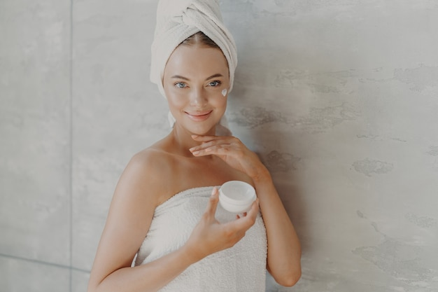 Indoor shot of happy young european woman applies anti aging cream on face, enjoys facial treatment after taking shower, wears bath towel on head and around naked body, poses against grey wall