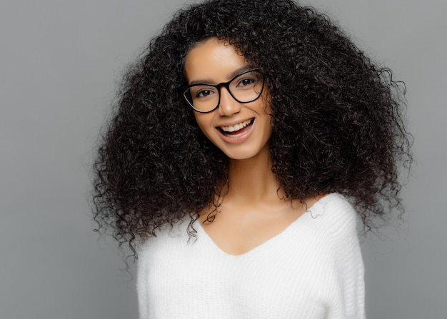 Indoor shot of happy young lady has afro hairstyle, smiles broadly, glad to be promoted, wears optical glasses and white sweater