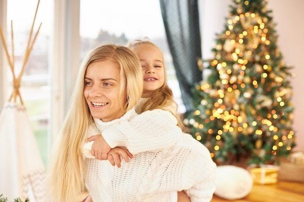 Indoor shot of happy young woman with long hair giving piggy back ride to her adorable little daughter, having fun, fooling around in living room with decorated shining christmas tree