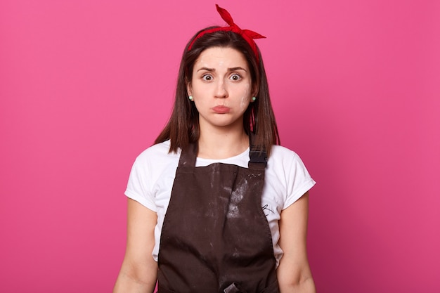 Indoor shot of hard working busy european housewife posing isolated over pink