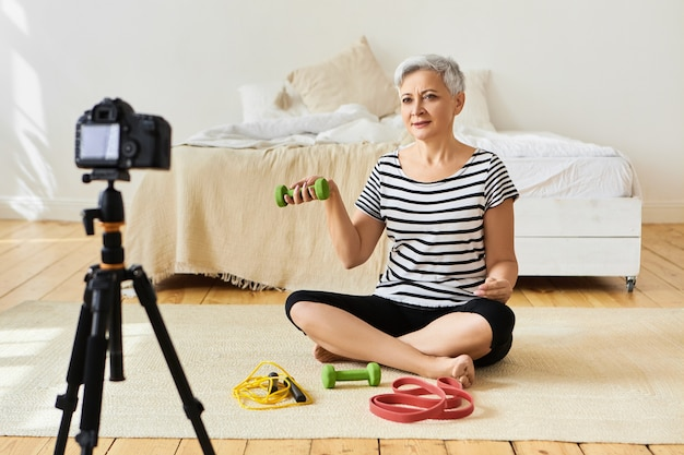 Indoor shot of healthy retired female in stylish clothes sitting on floor in bedroom in front of camera tripod stand, shooting fitness video tutorial for aged people, showing exercises with dumbbells