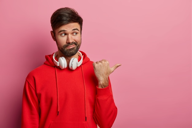 Indoor shot of hesitant unshaven man indicates aside, has doubtful look aside, asks whether to go there, wears headphones around neck, dressed in red hoodie, poses against pink pastel wall
