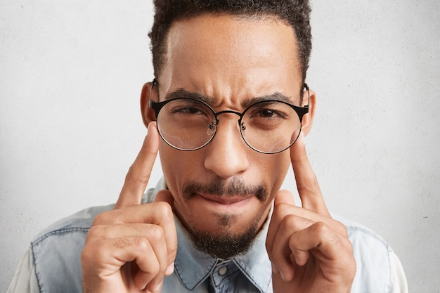 Indoor shot of hipster guy in round spectacles keeps fingers on temples