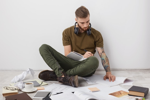 Indoor shot of hipster male with trendy hairstyle, thick berad and tattooed arms, looks attentively at book