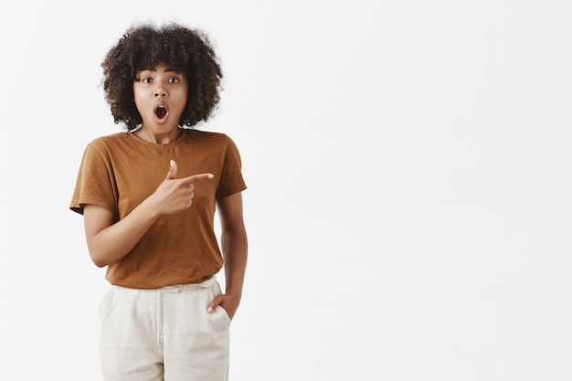 Indoor shot of impressed emotised good-looking young african girl with curly black hair dropping jaw from amazement pointing right with finger gun and asking question about what she sees