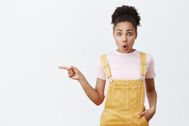 Tiro al coperto di una bella donna afroamericana espressiva in tuta gialla, che lascia cadere la mascella per lo stupore, piega le labbra e indica lo spazio della copia a sinistra sopra il muro grigio