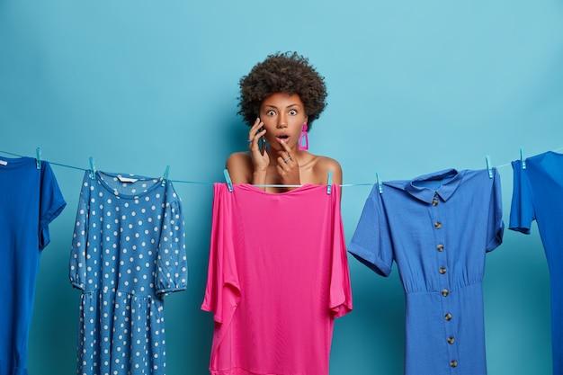 Tiro al coperto di una giovane donna colpita parla tramite smartphone, sta nudo dietro il vestito rosa sulla corda, posa vicino a vestiti diversi, isolato sulla parete blu concetto di abbigliamento e vestirsi.